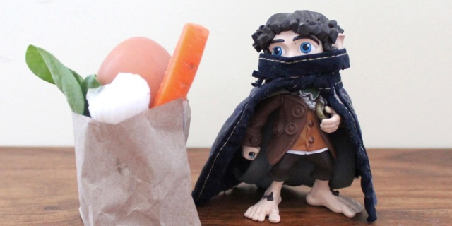 A feature image showing a toy Anti-Fascist wearing a face mask and cape near a bag of fresh produce.