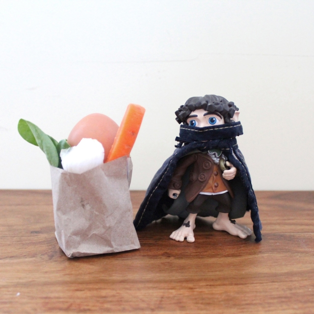 A small toy Anti-Fascist in a face mask and cap stands triumphantly next to a paper bag filled with fresh produce.