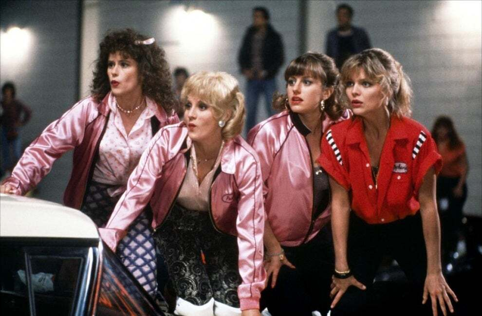 Still from Grease 2. 4 girls wearing Pink Satin Jackets and one in a red bowling shirt, all lean atop a car.