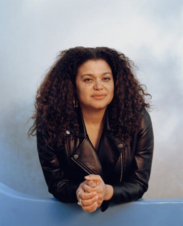 A photo of actress and writer Michelle Buteau. She is wearing a black jacket and her hands are clasped together as she leans forward and stares into the camera. Her soft curls frame her face with a soft gray background behind her.