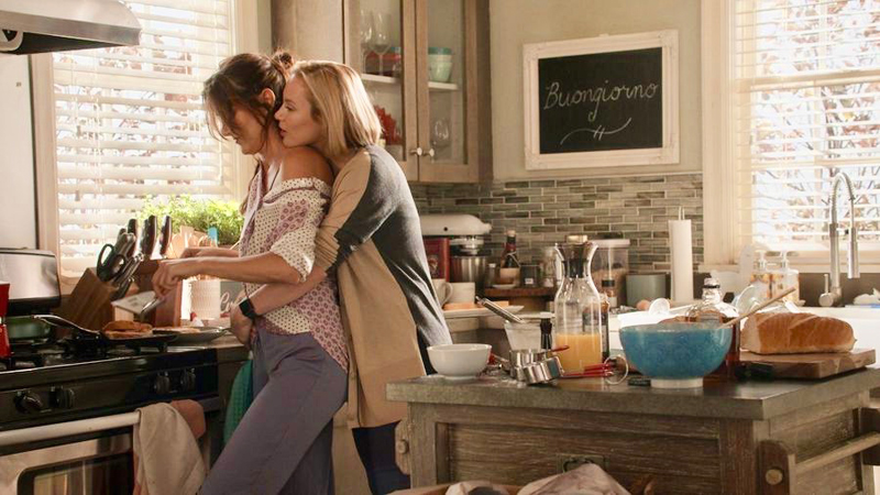 "In a still from the television show ""Station 19"" Maya, a short blonde woman with a bob hair cut, wraps her arms around her girlfriend Carina, who is a tall brunette with her hair in a messy ponytail. They are standing together in their kitchen while Carina cooks breakfast."