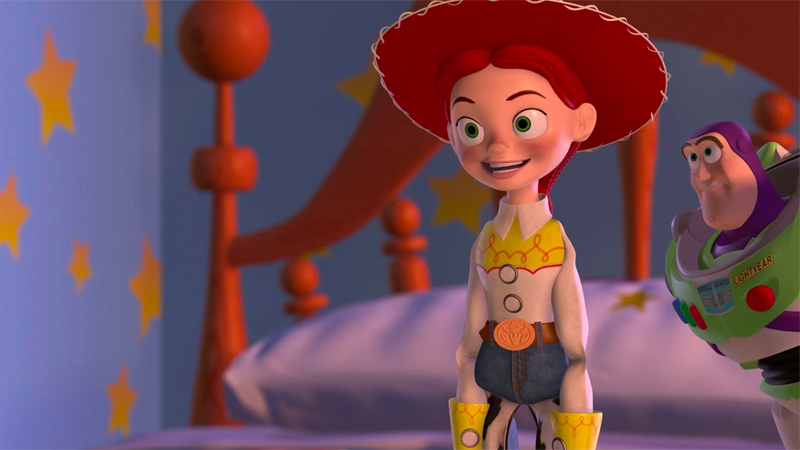 Bisexual Disney character/horse girl Jessie stands on Andy's bed in her cowgirl hat looking excited. She is the only Toy Story toy on the Bisexual Disney Characters list.