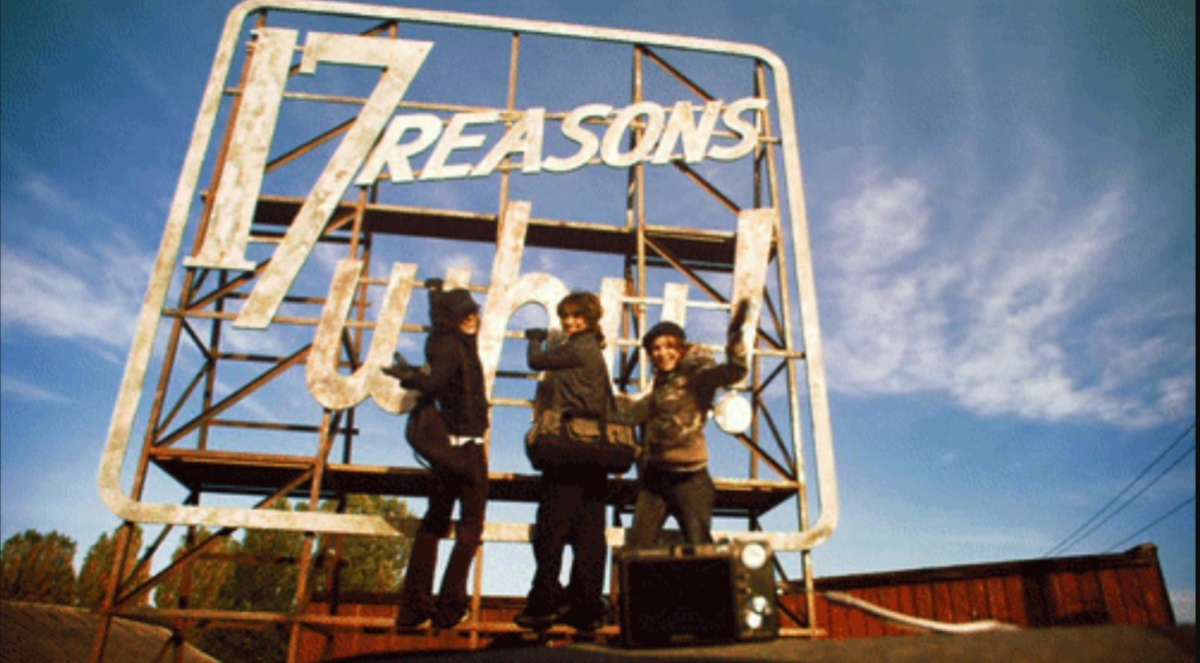 A scene from The L Word with Bette, Shane and Alice stood in front of a sign that says 17 Reasons Why