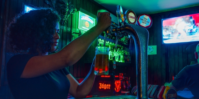 A woman with curly hair in a dark bar pours a draft from a spigot.