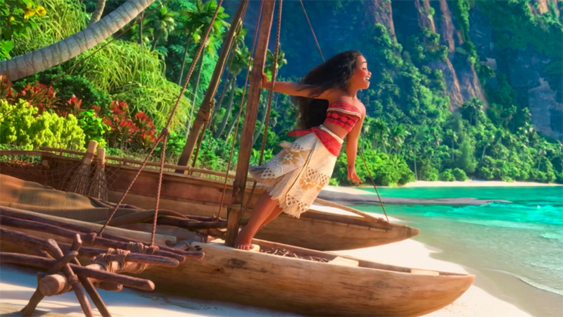 Moana stands on a boat on the shore and sings.