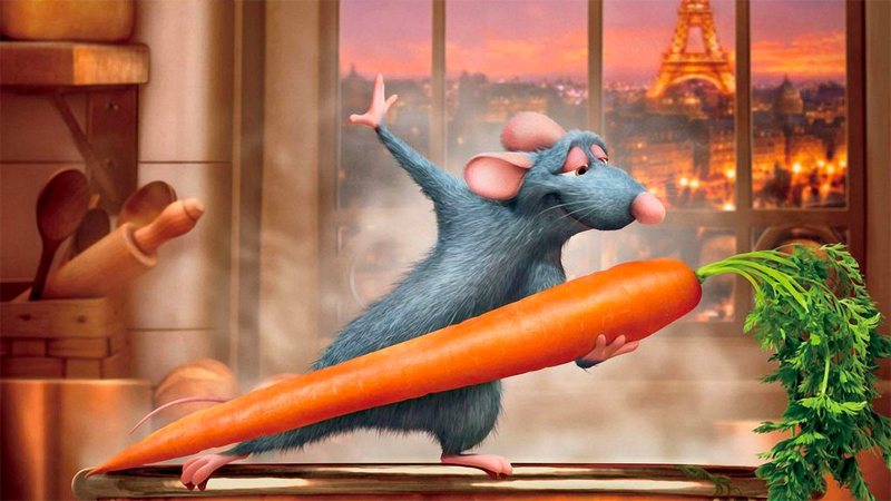 Remy dances with a carrot in front of a window with the Eiffel Tower in the background.