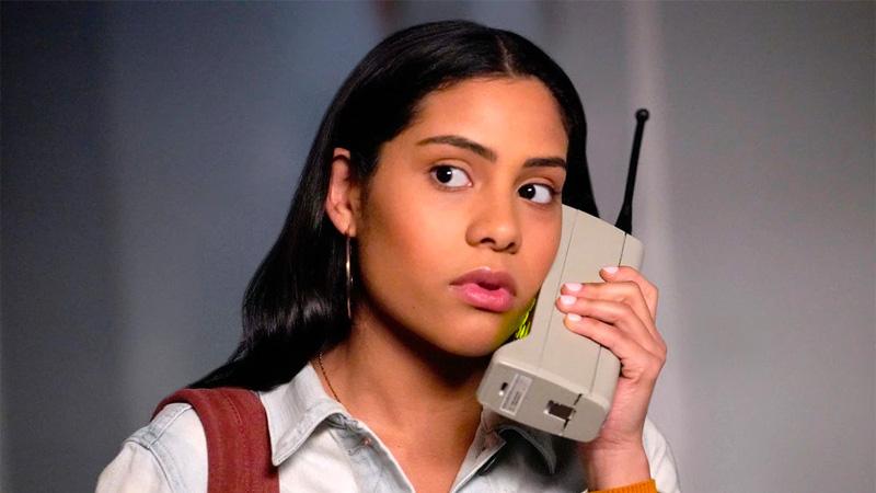 Daisy (Haskiri Velazquez) talks on a huge '90s cell phone.