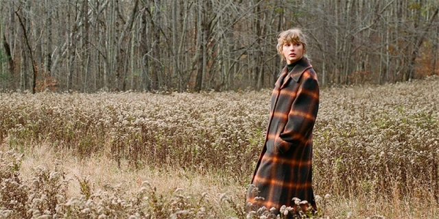Taylor Swift stands in a field in a cottagecore-esque peacoat for Evermore.