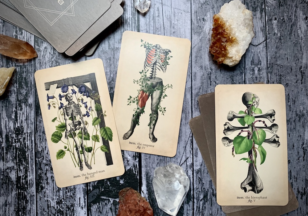 Three cards representing the Hanged Man, the Emperor, and the Hierophant