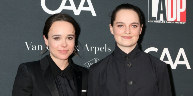 Elliott Page and their partner Emma on a red carpet event, both have their hair slicked back into low bungs and have on black suits with black collared shirts underneath.