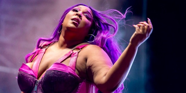 Lizzo in a purple wig is performing on stage in a hot pink bra.