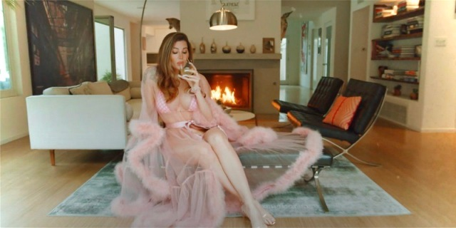 "Trace Lysette sips wine in a see through flouncey pink robe in a still from her music video, ""SMB"""