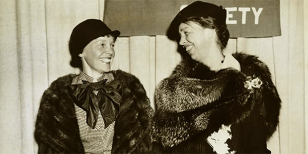 Amelia Earhart and Eleanor Roosevelt stare lovingly at each other and smile in this vintage photograph.