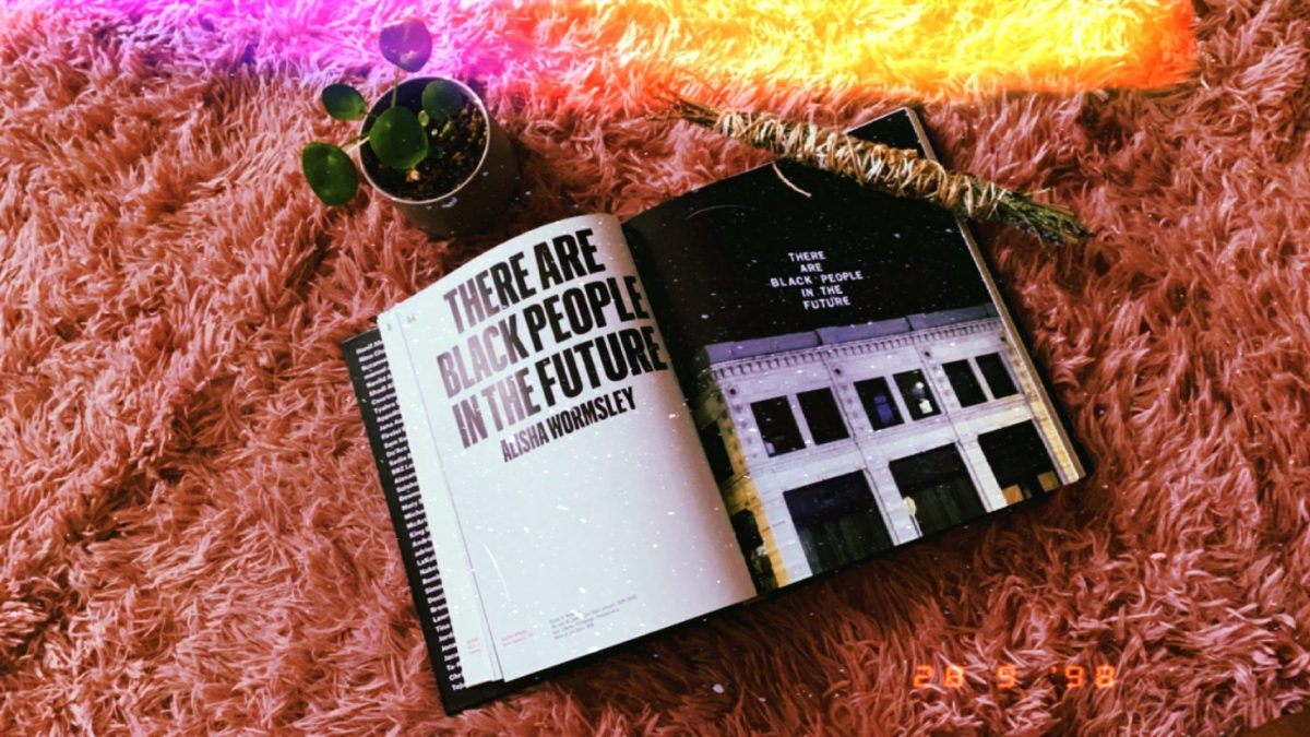 """Image shows an excerpt from the book """"Black Futures"""" called """"There are black people in the future"""". There is a cleansing bundle and a small plant in the frame."""