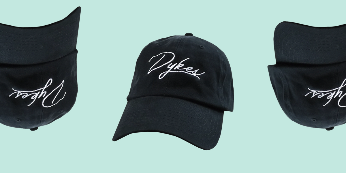 """A black baseball cap with black stitching. In white embroidery the word """"Dykes"""" loops elegantly on the front."""