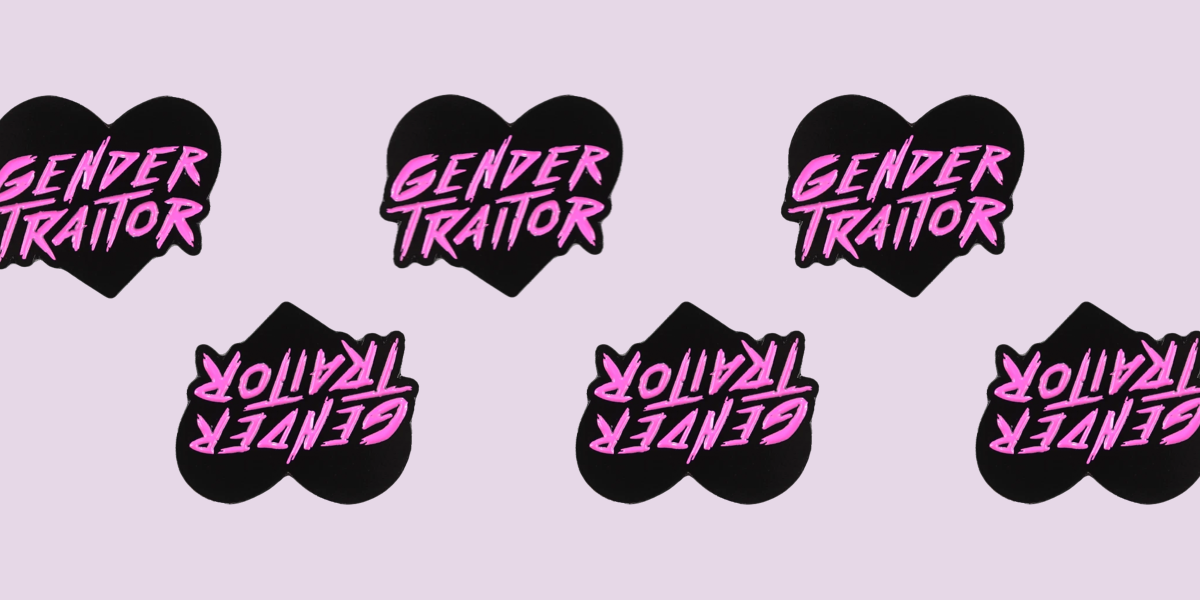 A black and pink heart shaped enamel pin. The words GENDER TRAITOR are in a textured painted typeface.