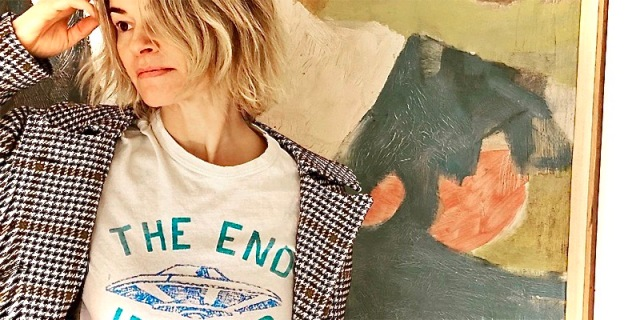 "Leisha Hailey in a t-shirt that says ""the end is near"" with an alien spaceship in blue. She is standing next to a piece of green and yellow art."