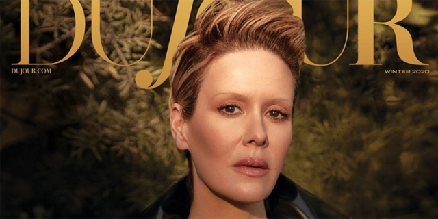 Sarah Paulson is on the cover of Dujour Magazine. Her blonde hair is slicked back and to the side. She has on neutral make up that has matted down her eyebrows, so they look invisible.