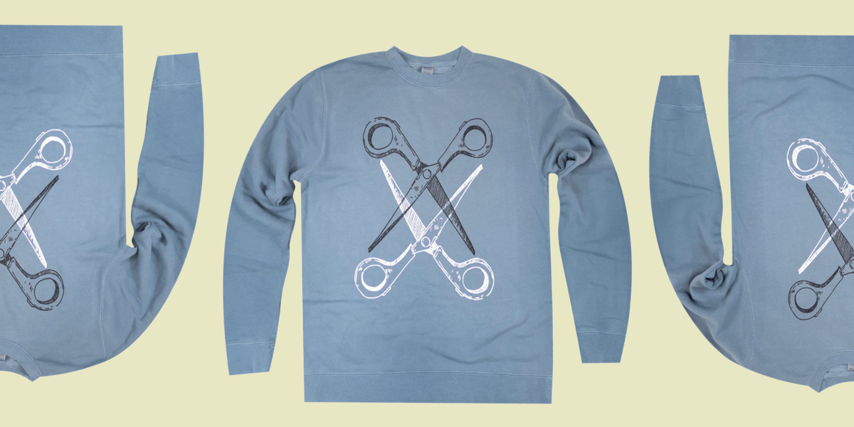 Scissoring sweatshirt is a classic cut in a medium blue tone. Two pairs of scissors — one black and one white — intersect.