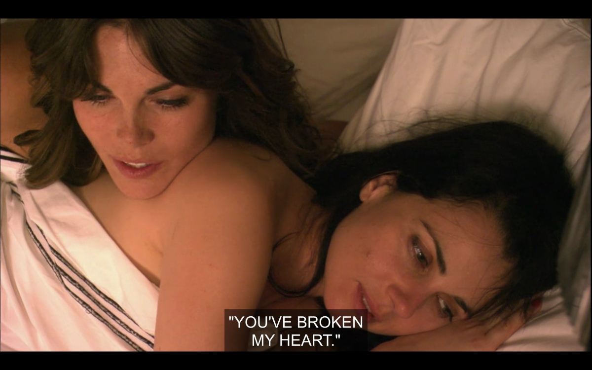 "Nikki leaning on Jenny's shoulder in bed, naked, quoting Jenny saying ""you've broken my heart"""