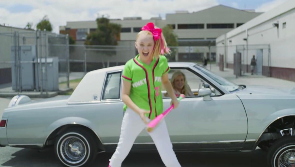 JoJo in a music video wearing a baseball uniform in front of a car