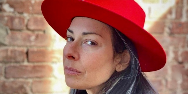 Stacy London in a boss looking bright red wide brimmed hat against a brick background with just a perfect streak of sunlight against her face.