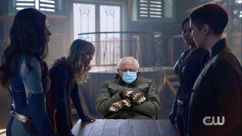 Cut out Bernie Sanders sits at a wooden table while everyone plots how to take down a villain on Supergirl