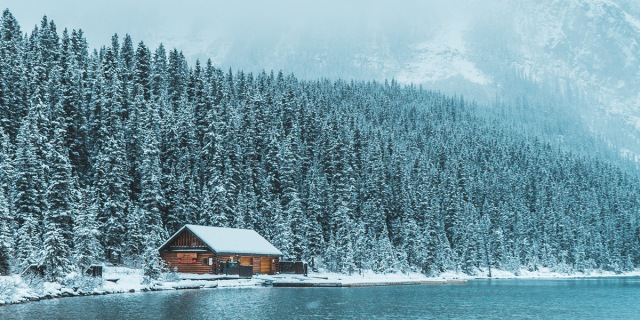 Image shows a Cabin far off in the woods. Mountains are in the background and it is sitting right off a lake - snow covers everything