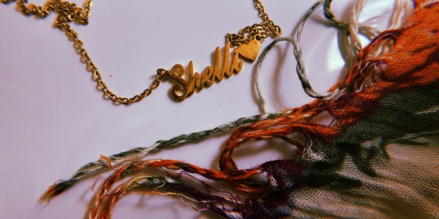 Image shows necklace that reads Shelli with the edges of a scarf around it.