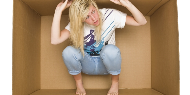 A blonde woman in a white T-shirt and jeans is trapped inside a cardboard box.