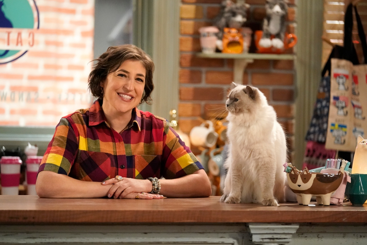 Mayim Bialik sits with a cat on the counter of the cafe she owns in Call Me Kat.
