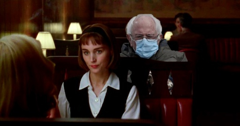 "A cut out of Bernie Sanders peers over Therese's shoulder during lunch in a 1950s bar in ""Carol"""
