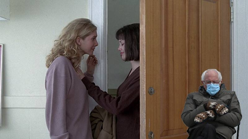 A cut out of Bernie Sanders creeps behind the door while Gia flirts with her girlfriend in the movie Gia