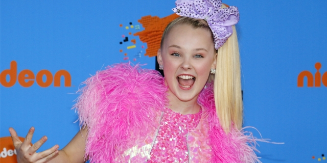 JoJo Siwa wears a purple hair bow and pink outfit made of feathers and sequins.