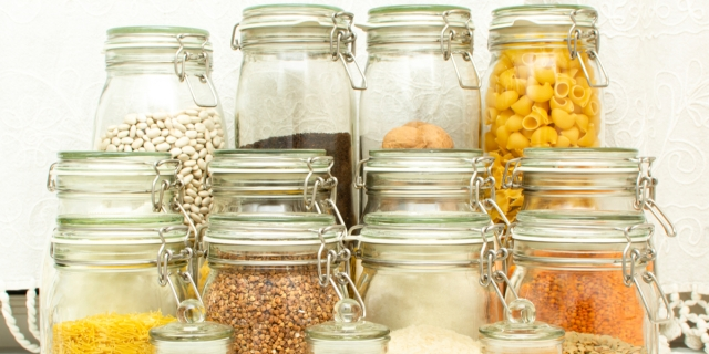 A close up photo of sealed jars packed with dry goods