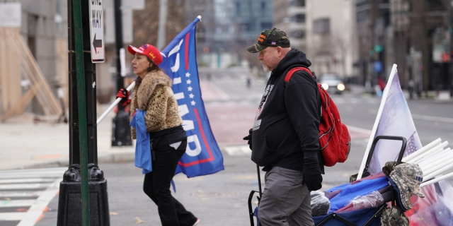 Two white people carry Trump flags and merchandise in their hands and a rolling wagon while wearing MAGA hats in DC on the morning of January 6, 2020.
