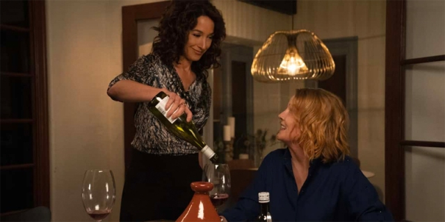 Bette pours Tina a glass of wine in season one of The L Word: Generation Q.
