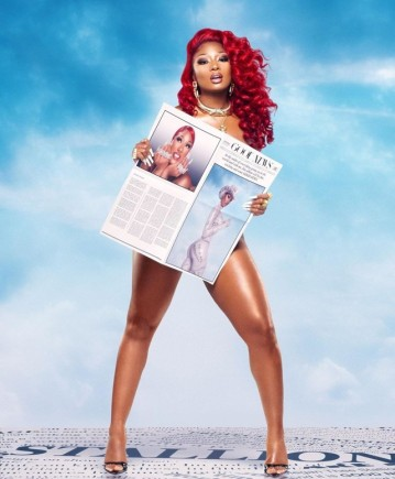"Image shows Megan Thee Stallion standing facing the camera with her red hair flowing down. She is holding a paper with her face on it and the words ""Good News"" across the top."
