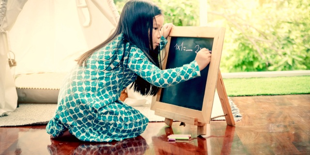 A young girl is in a green dress and bent off a chalkboard as she works on a math problem against a spring background, it looks serene.