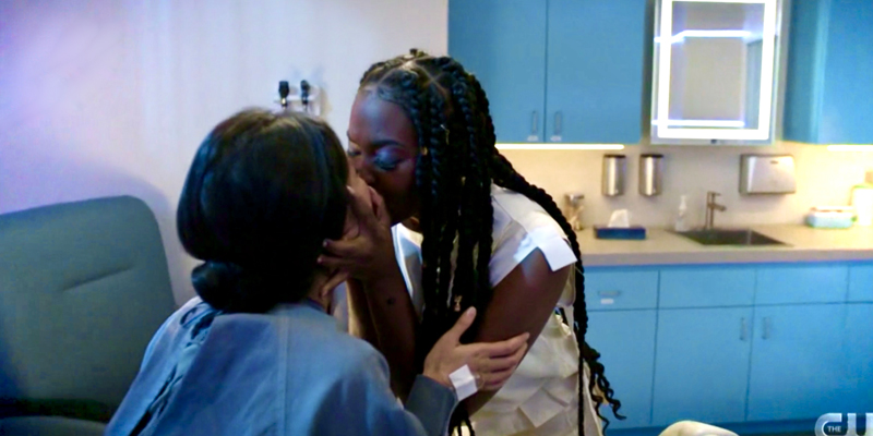 Anissa Pierce holds Grace Choi's face in her hands and kisses her, long and hard. They are in Grace's hospital room, which has pale purple walls and blue cabinets. Anissa's hair is in long braids and she wears a white blouse, Grace's hair is pulled back into a bun and she wears a hospital gown.