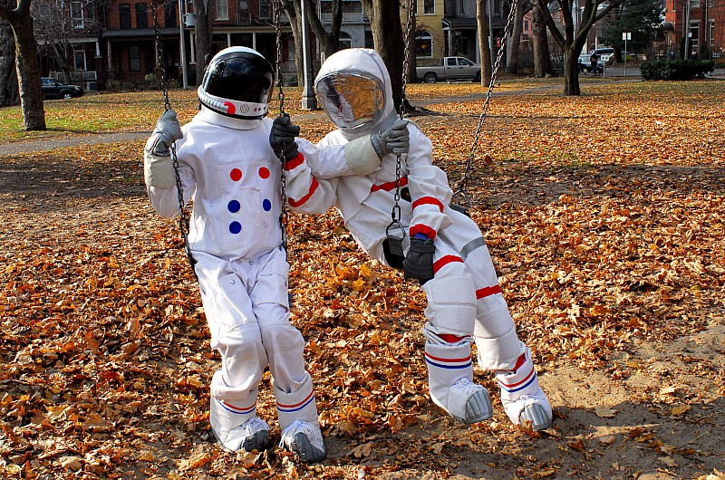 Two figures in spacesuits sit on a swingset in a sunny park full of fall leaves, one leaning toward the other as if to embrace them