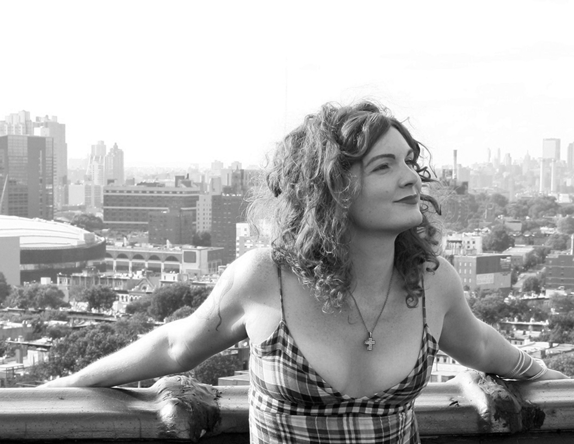 A black and white photo of Bryn Kelly, a women with culry hair wearing a cross necklace and sundress, smiling on the roof of a building
