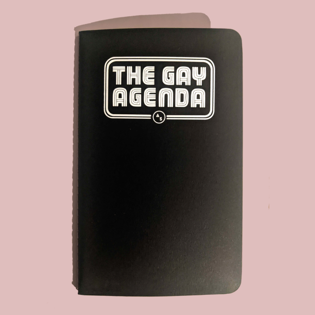 "A black softcover journal with ""the gay agenda"" printed on the front"