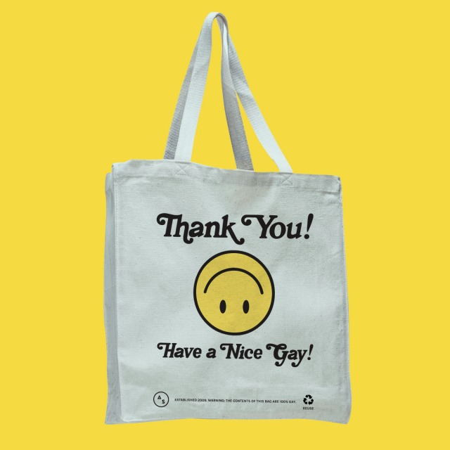 A white tote bag with Thank You! Have a Nice Gay printed on it, with an upside down smiling emoji