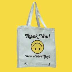 """a white tote bag with an upside down yellow smiley face. The bag reads """"Thank You Have a Nice Gay!"""""""