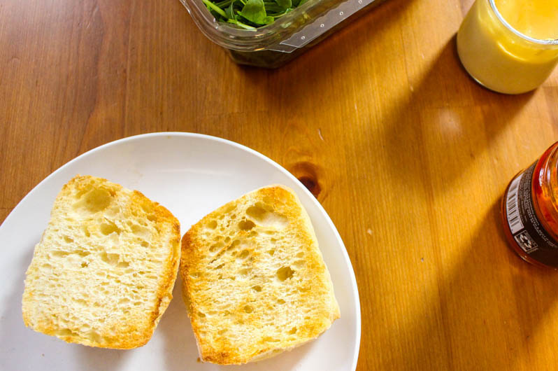 A photo of two halves of a ciabatta roll toasted on a wooden kitchen table