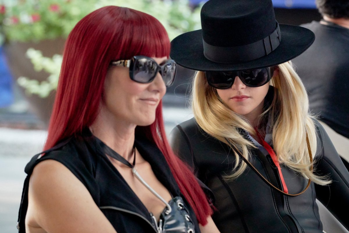 Kristen Stewart in a black hat and blonde wig and sunglasses sitting next to laura Dern in a bright red wig with severe bangs