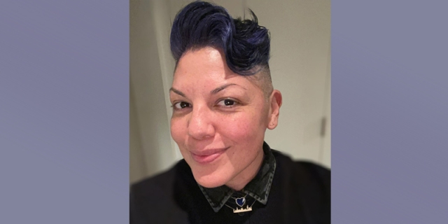A selfie of Sara Ramirez with their signature hair cut died a dark lavender purple. They are smirking at the camera, full of pride and mischief.
