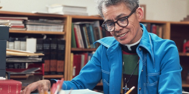 Pauli Murray wears glasses and short cut grey hair with a denim blue overskirt while smiling and writing in a library in front of books.