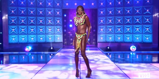 Symone walks down the Drag Race runway and she looks gorgeous in an beaded two piece (bikini top and skirt) inspired by West Africa. Her hair is braided down behind her back, also adorned with beads.